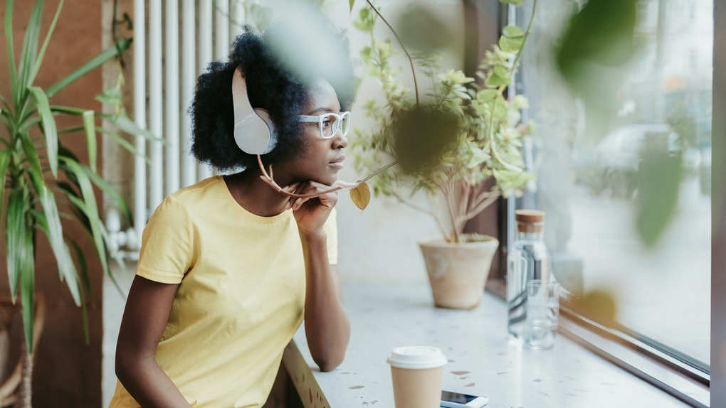 Side view of thoughtful young American girl situating near windowsill and looking through the window. She is wearing modern headphones and listening to music