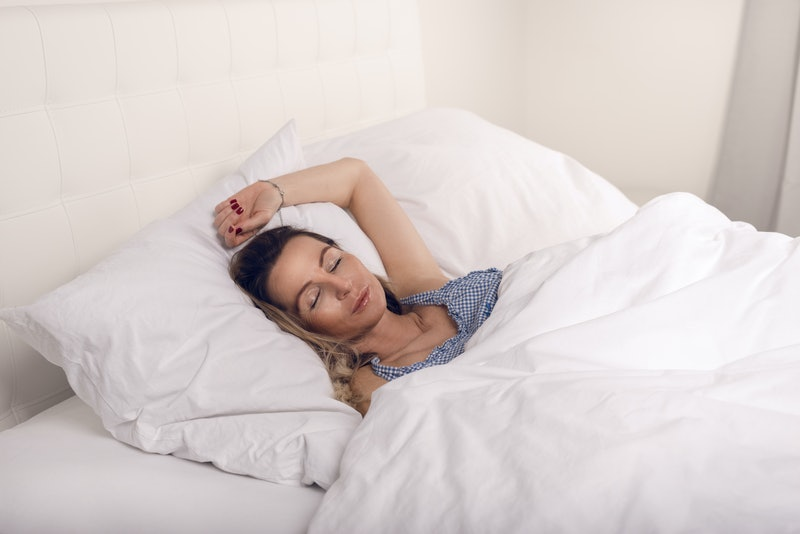 Woman sleeping in bed under white quilt with head on pillow
