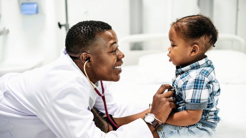 Cheerful pediatrician doing a medical checkup of a young boy