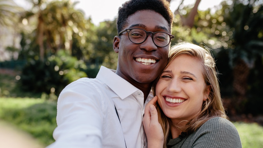 Beautiful interracial couple making a selfie outdoors. African man with caucasian woman taking a self portrait.