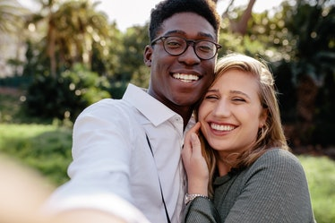 Beautiful interracial couple making a selfie outdoors. African man with caucasian woman taking a sel...