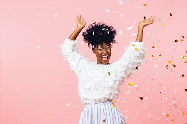 Fun party girl, smiling woman throwing confetti