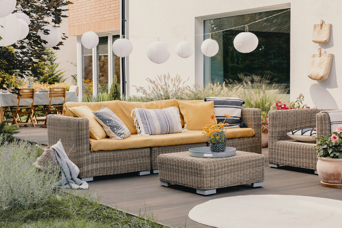 Real photo of a rattan garden furniture set with lamps and table in the background