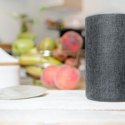 Personal assistant connected loudspeaker on a wooden table in a Smart Home in a kitchen. Next, some utensils, food and fruit. Empty copy space for Editor's text.
