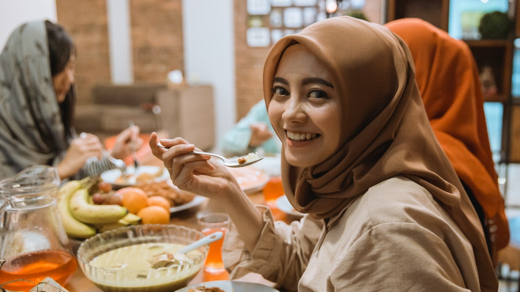 beautiful asian muslim woman smiling to camera while having dinner together with family