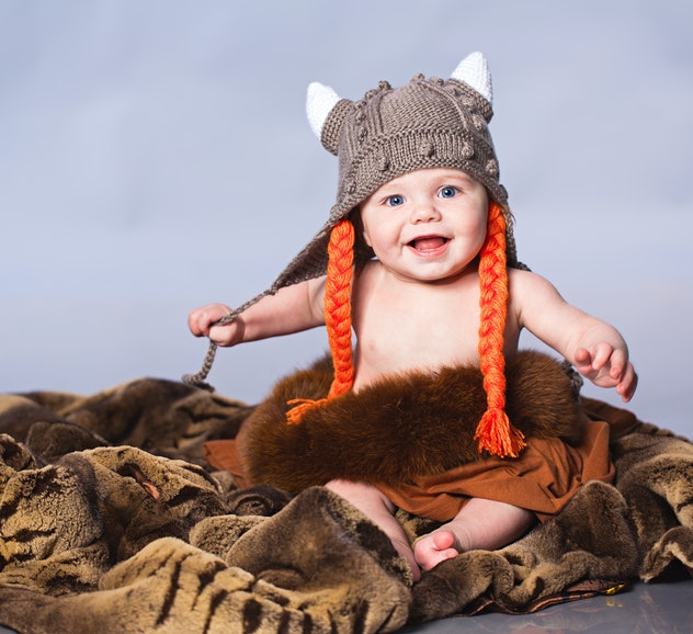 Little boy sitting on the fur in viking style hat