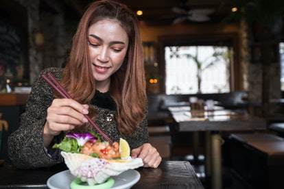woman eating salmon sashimi spicy salad in the restaurant