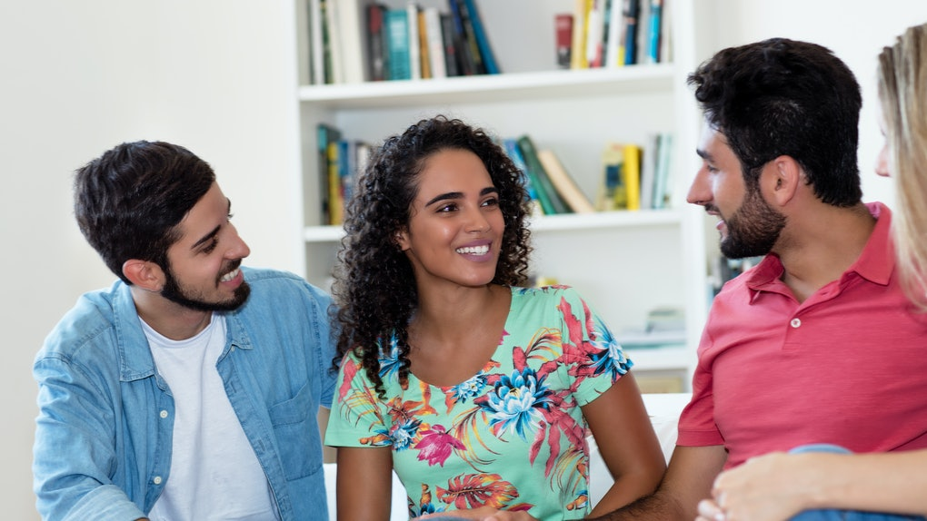 Latin american man and woman talking with group of friends indoors at home