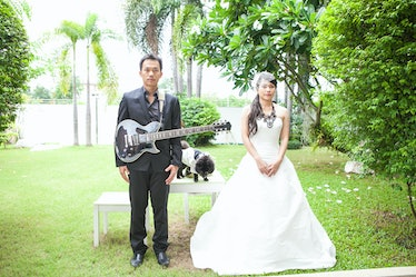 Bride and groom is happy play guitar in the lawn with dog