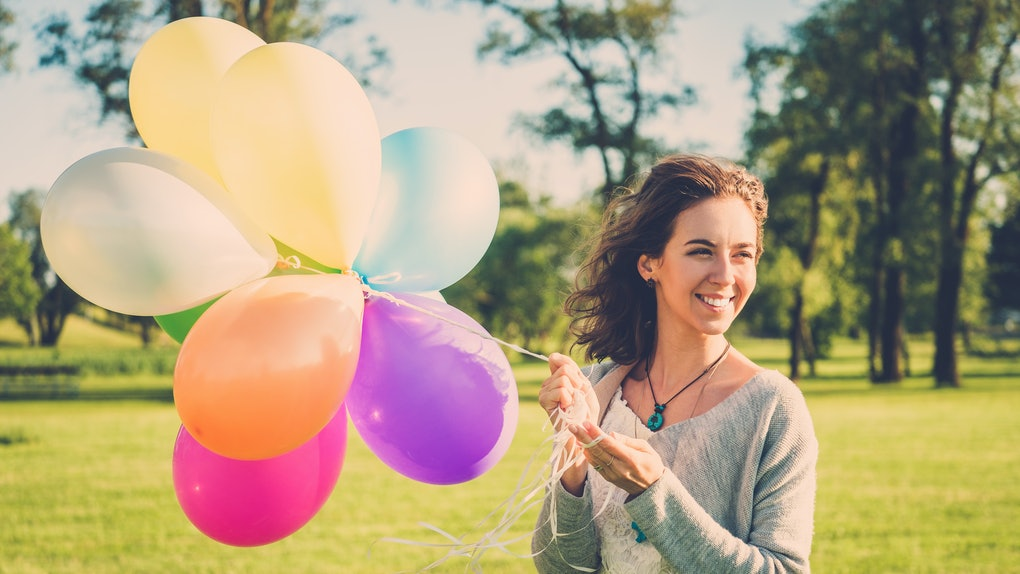 Girl with rainbow-colored air balloons in a park.