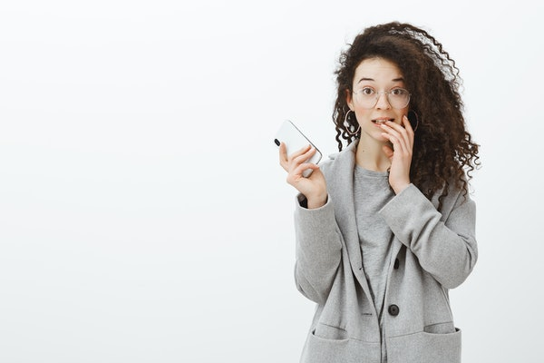 Portrait of embarrassed cute curly-haired female student in stylish grey coat and glasses, holding smartphone, lifting eyebrows and biting finger, making mistake and feeling awkward over gray wall
