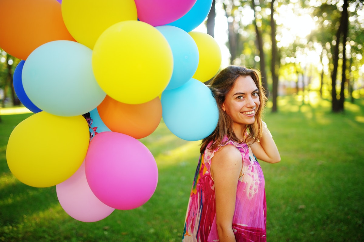 Beautiful, cheerful young woman in a bright dress with colorful balloons in a park with green grass ...
