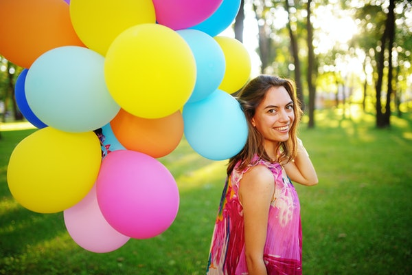 Beautiful, cheerful young woman in a bright dress with colorful balloons in a park with green grass in the summer. Warm sunny summer day with light breeze.