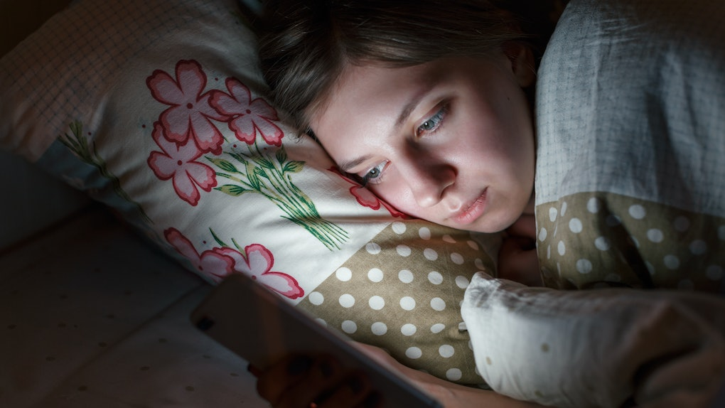 Sleepy woman awake late at night in bed surfing in web, can not fall asleep/ sleepy tired, social media addiction, dependency on cell phone, half-closed tired eyes, insomnia, sleeplessness concept.