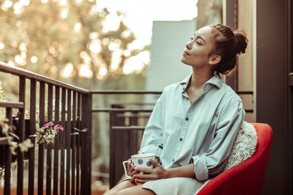Drinking morning coffee. Peaceful good-looking woman in oversize male shirt carrying big cup while s...