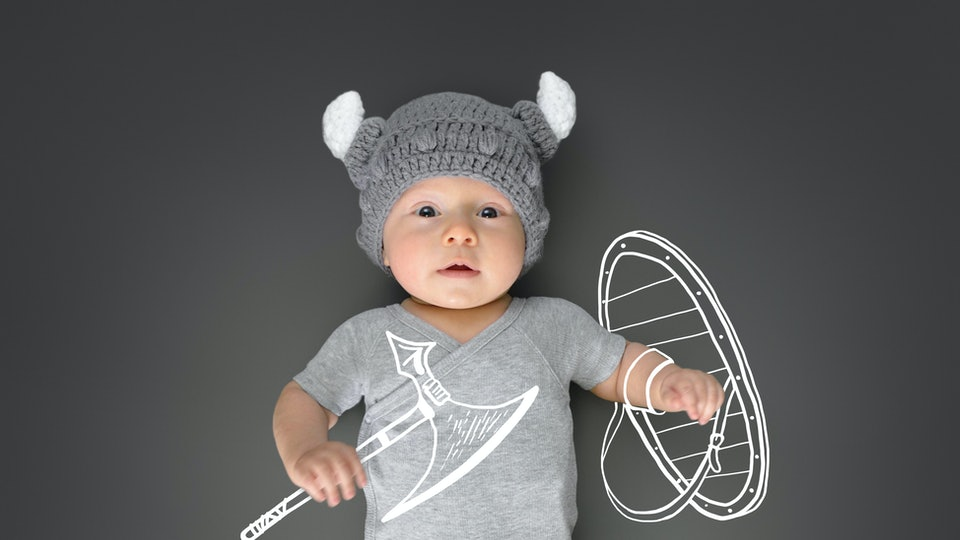 Three month old baby in viking's hat lying on a play mat and pretending he is a real viking warrior