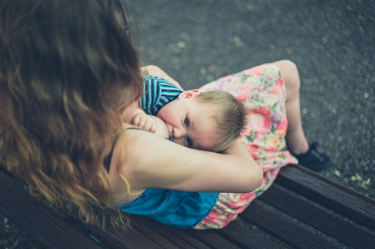 A young mother is breastfeeding her baby on a park bench