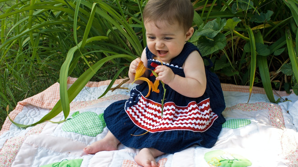 Caucasian baby girl wearing patriotic dress outside in tiger lillies