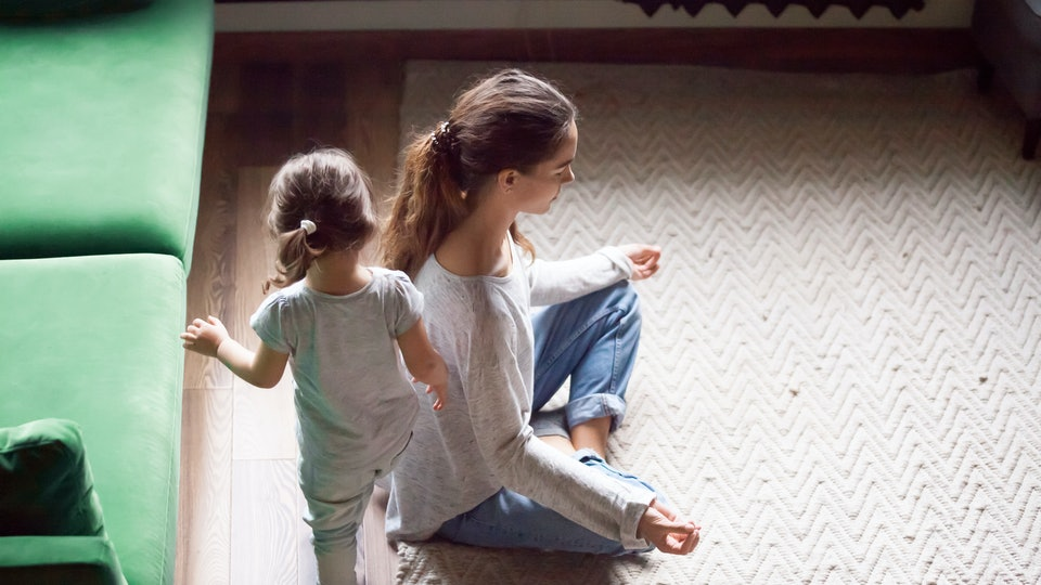 Young single mother doing yoga exercise, meditating while little preschool daughter running, playing, no stress, relax, tired mum sitting in yoga pose, emotions control, motivation, calm mind concept