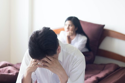 Asian man, who wear white shirt on red bed with angry wife,  feeling disappointed and depressed because of erectile dysfunction.