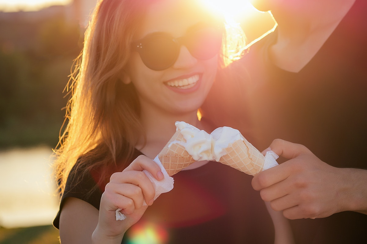 happy californian couple in love in summer park. beautiful woman and handsome man eat ice cream in a waffle horn cone at sunset on the beach. cool photosession photoshoot of young family