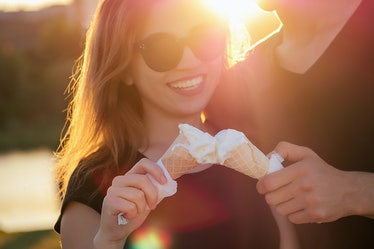 happy californian couple in love in summer park. beautiful woman and handsome man eat ice cream in a...