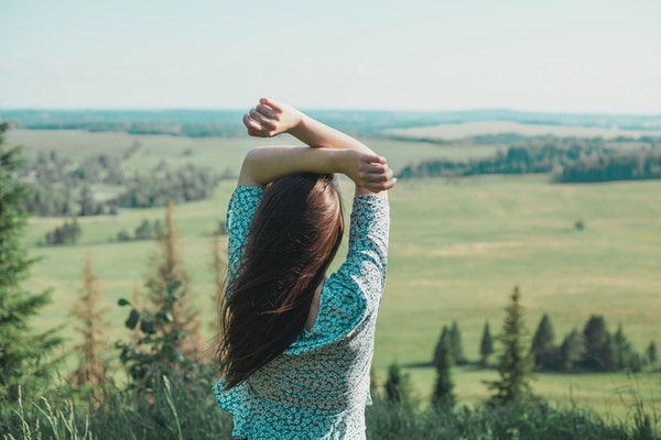 Girl in the nature enjoying fresh air and life in summer