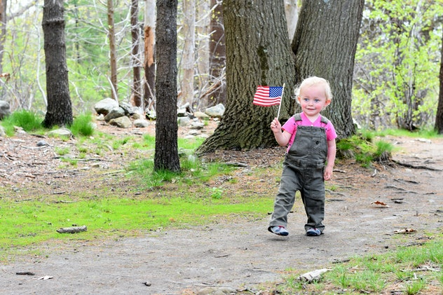 Young Boy Carrying American Flag Outside