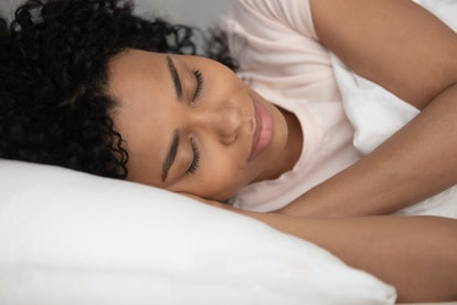 Calm black woman sleeping well in comfortable bed, young serene healthy african girl beautiful face resting in good night sleep lying on soft pillow white linen orthopedic mattress, close up view