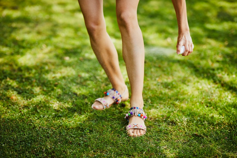 Close-up of young woman's legs being sprayed with insect repellent outdoors