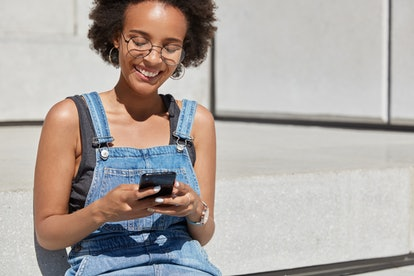 People, recreation and technology concept. Relaxed carefree black woman holds cell phone in hands, t...