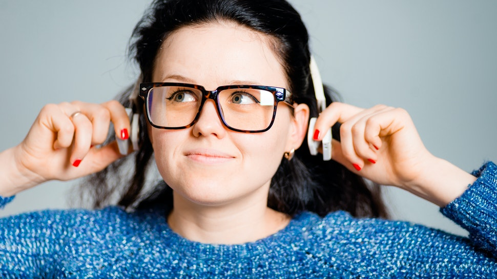 business woman listening to wireless headphones isolated on gray background