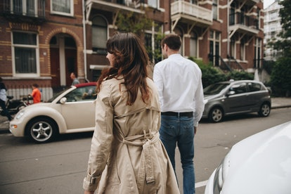 couple walks in Amsterdam. Old city. Love story. Walk around city. Brown-haired girl in beige trench coat. The guy in shirt and jeans. Run through the streets. Hide and sit on the steps of the house.