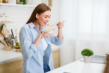 Healthy Eating. Woman Eating Corn Flakes Having Breakfast In Kitchen