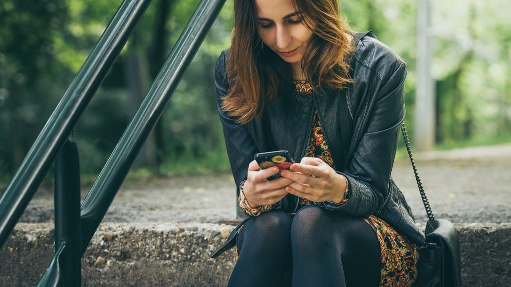 Woman looking at cell phone with worried expression on face.