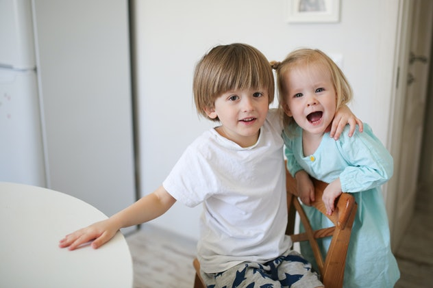 brother and sister siblings tenderly embrace on a light background in a real interior, the concept o...