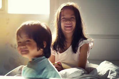 Soft focus image of Kids in their bedroom.The warm climate of Asian mixed race sibling wake up in the morning,spent their time together.Selective focus.Image with noise and grain.Warm climate concept.