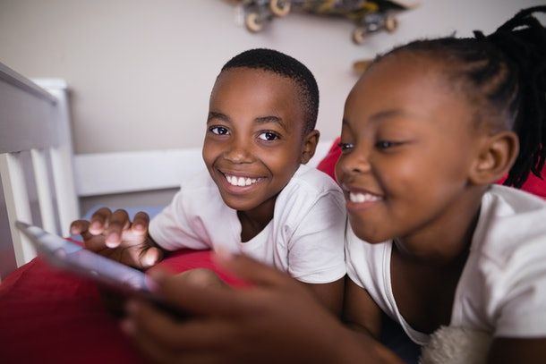 Close up of happy siblings using mobile phone while lying on bed at home