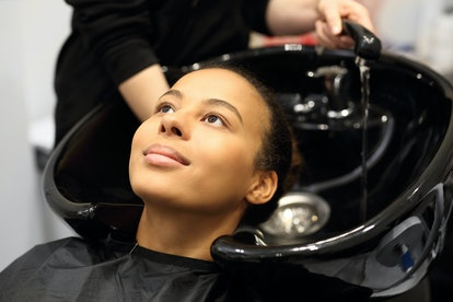 Washing head in a hair salon. Hairdresser washing hair woman