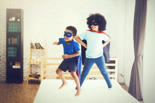 African American happy and confident young kids playing  and dressing up as superhero together in b...