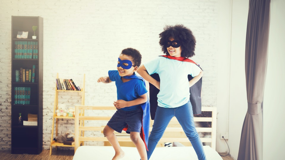 African American happy and confident young kids playing  and dressing up as superhero together in bedroom