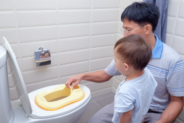 Father Training sleepy son to use toilet in bathroom, Cute little Asian 1 year old / 18 months toddler baby boy sitting on toilet with kid bathroom accessory, Potty / Toilet Training child concept