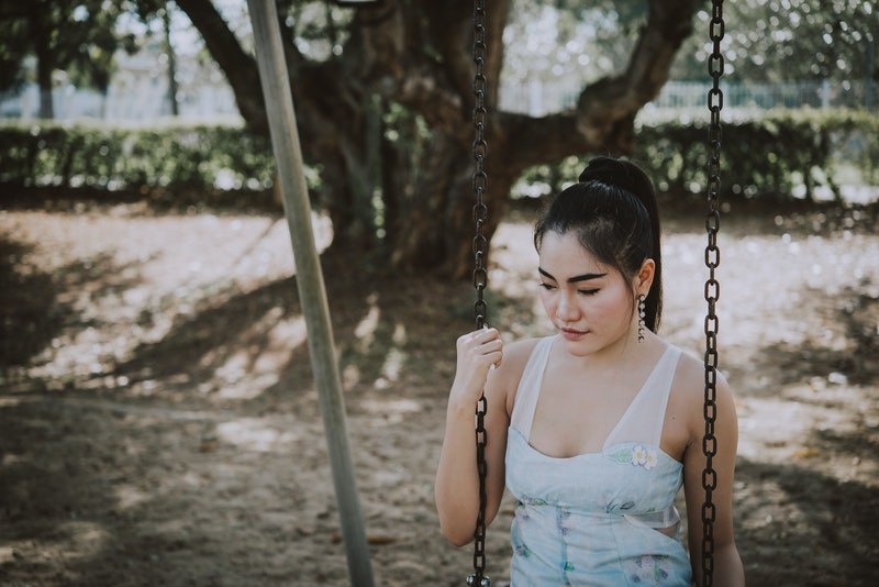 Portrait of sad asian woman cry in the park,Thailand people heartbreak concept