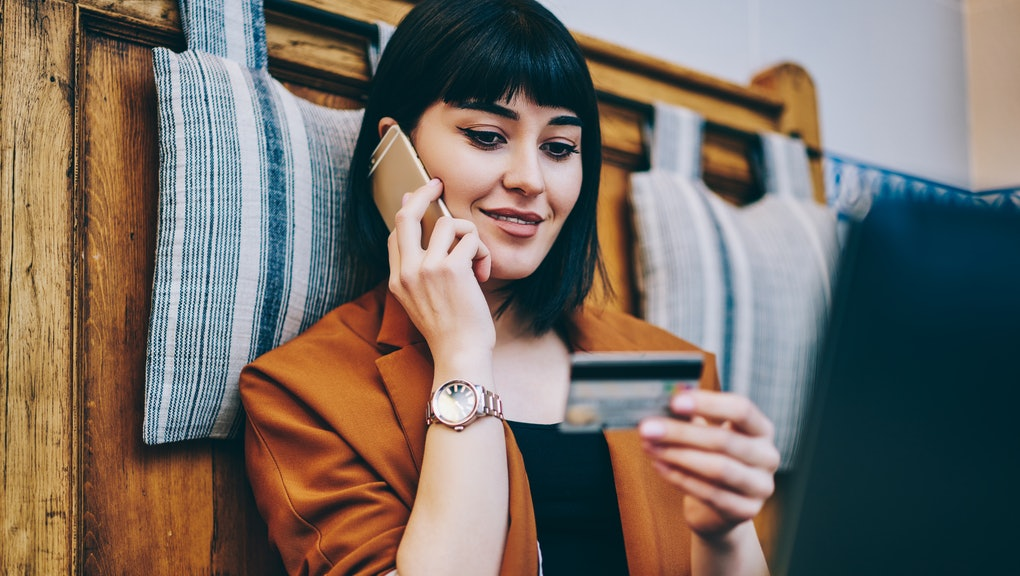 Positive woman looking at number on credit card and confirm purchase via telephone call to customer service, smiling hipster girl making payment via smartphone conversation while resting indoors