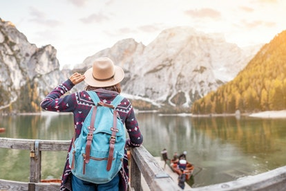 Asian woman traveler on the shore of the famous tourist lake Braies in the Dolomites Alps, Italy. The concept of travel and adventure in the mountains at autumn season
