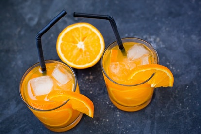 two glasses with an orange drink and an orange slice  with tubules on a dark concrete background close-up