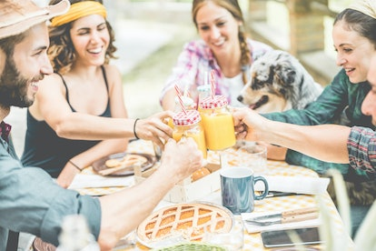 Happy millennial friends cheering at breakfast brunch meal in nature outdoor - Young people having fun together eating fruits and drinking smoothies - Summer concept - Focus on close-up glasses