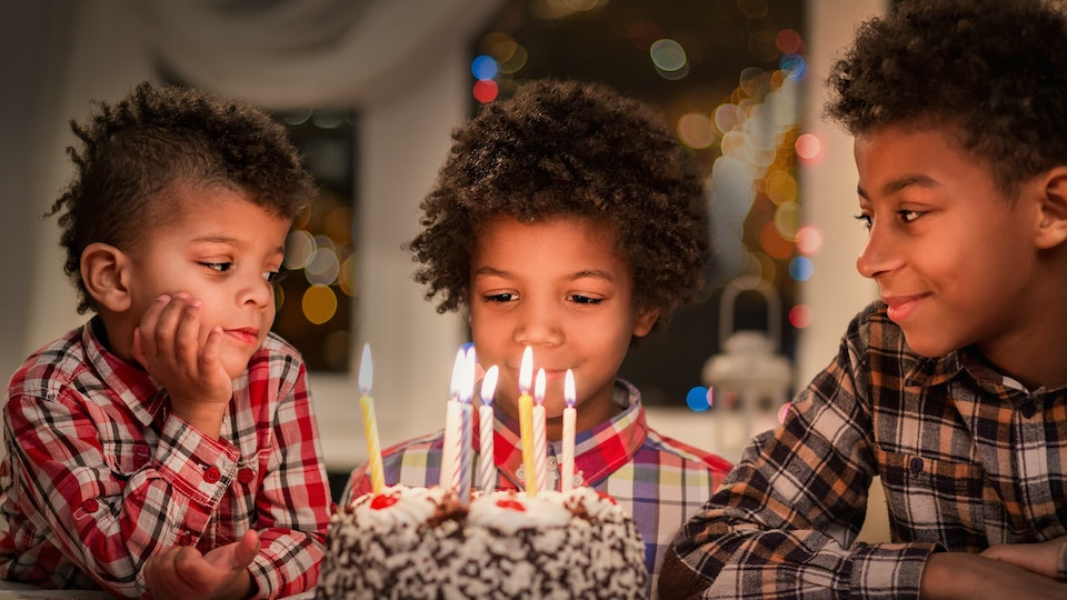 Black children with birthday cake. Three boys at birthday table. Happy birthday, brother. Watching the candles burn.