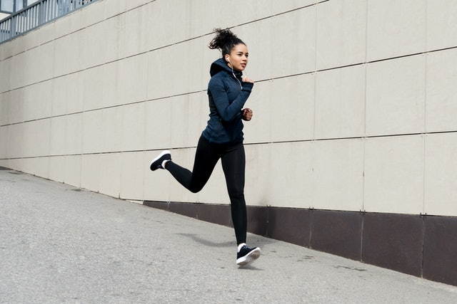 Fit brunette woman running in the city