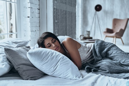 Lost in a deep sleep. Attractive young woman keeping eyes closed while lying on the bed at home